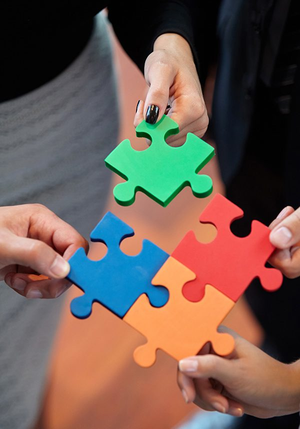 Group of business people assembling jigsaw puzzle and represent team support